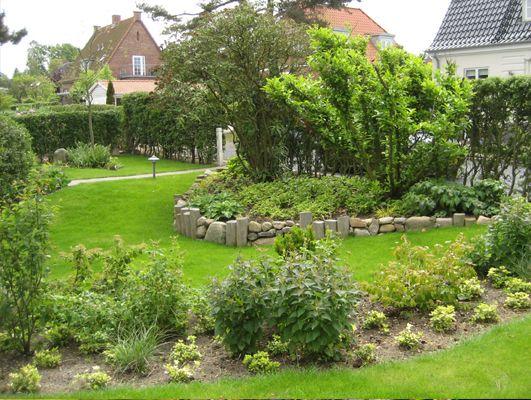 Havedesign ned til Lillebælt i Middelfart. Kantafgrænsning i form af robiniepæle og natursten. Organisk formgivning.