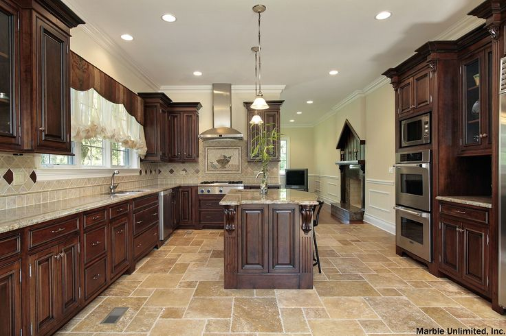 Huge kitchen with plenty of space to entertain and wow the friends. Traditional kitchen with dark wood cabinets, elegant lighting and stone tile flooring.