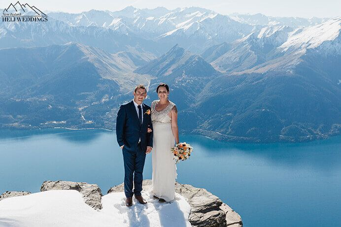 sunny spring day. bride and groom stand In snow on the ledge. Destination Heli weddings Queenstown.
