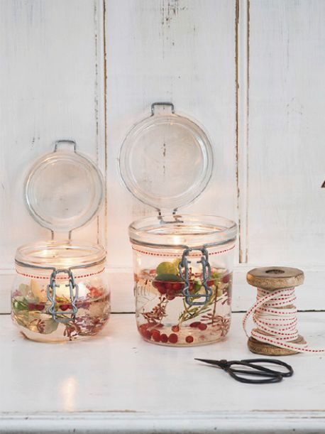 DIY Christmas Floating Candle Jars: wrap ribbon around top of jar, add berries, rosemary & eucalyptus to jars, fill w/ water, add floating candle & light.