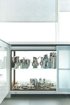 All mill-work designed, provided and installed by Yorkville Design Centre Base sliding glass door cabinets with glass backing. This allows for the natural light to shine through the cabinet from the large floor to ceiling windows featured in this kitchen.