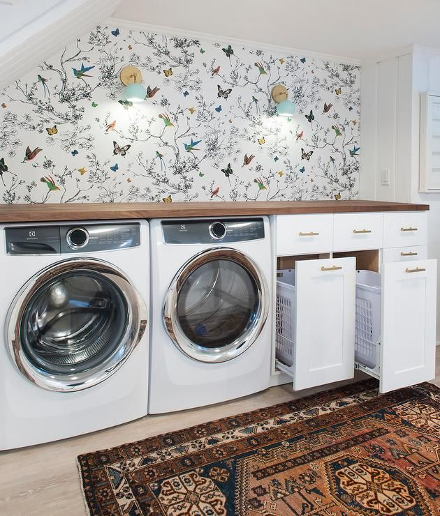 Fabulous, basement laundry room features a nook tucked under a staircase filled with a white front load washer and dryer and cabinets fitted with pull out hamper bins topped with butcher block lining a wall clad in Schumacher Birds & Butterflies-Multi On White Wallpaper illuminated by turquoise blue vintage wall sconces.
