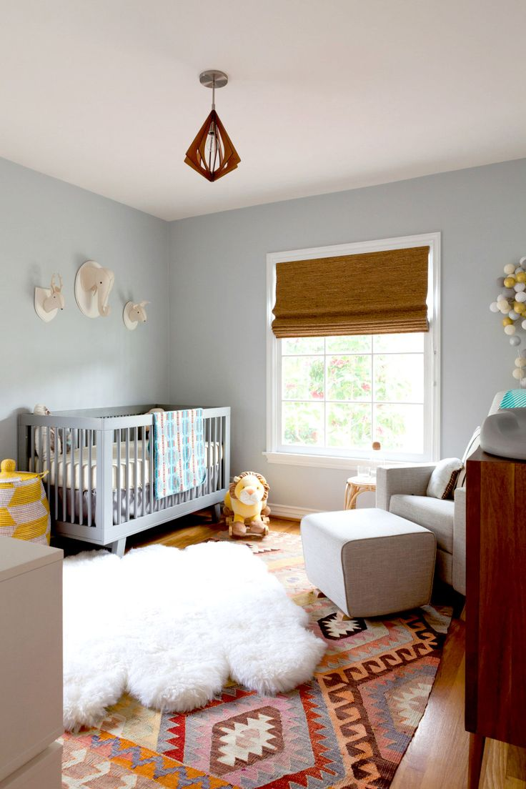 Pale blue kid's room with crib and wall decals - love this Kilim rug. Very Aztec-inspired nursery!
