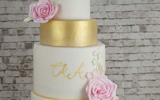 En guld glans og hvid bryllupskage med håndlavet sukker lyserøde blomster. Håndmalet guld monogram  Læs mere om vores kager på http://www.bakemydaydk.com  Bemærk at vi anbefaler at bestille bryllupskager hurtigst muligt efter forlovelsen.