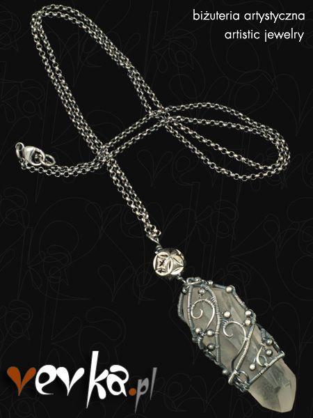 Intrygujący wisior wykonany z monokryształu kryształu górskiego oraz srebra prób 999 i 925. Wykonanie w całości ręczne przy zastosowaniu techniki wire wrapping. Kryształ pochodzi z Brazylii, a ze względu na swoje właściwości tego rodzaju kryształy są wykorzystywane w ezoteryce, reiki i litoterapii.
