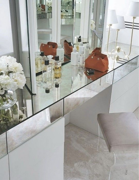 Beautiful dressing area features a white vanity with mirrored countertop with drawers adorned with fresh cut flowers and a contemporary three arm wall sconce on either side of a trifold vanity mirror over wall to wall beige carpeting topped with a lucite vanity stool.