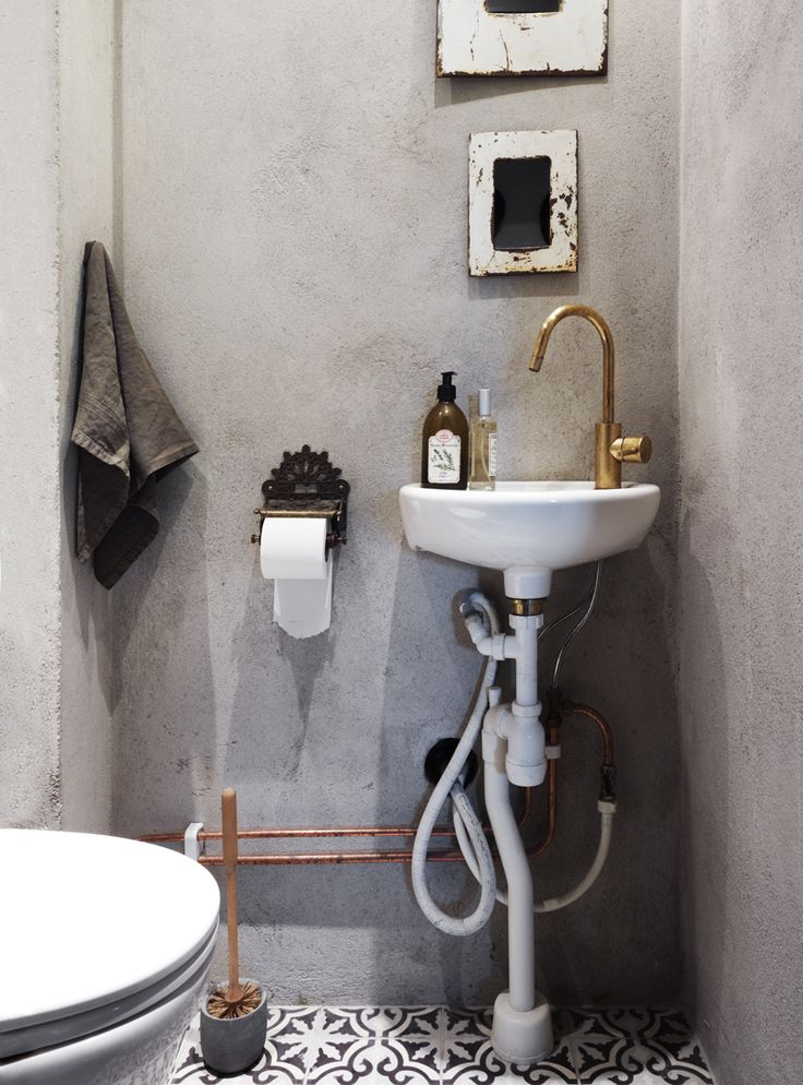 Industriell känsla i badrummet med betong och mässing. Color schemes - gray and black and copper. Toilet paper holder. Eclectic. Floor.