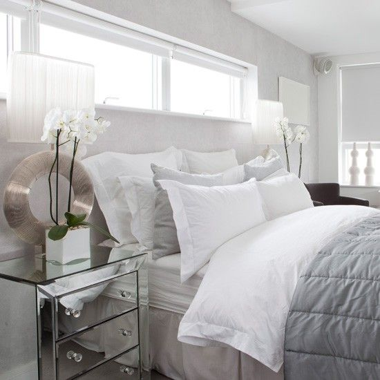 bedroom with mirrored furniture. stylish white bedroom blending icewhite walls bedlinen and roller blinds with cool dove grey accents gives a chic timeless appeal mirrored furniture