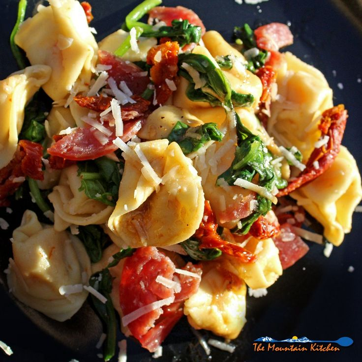 This Tuscan Tortellini Pasta Salad is loaded with with cheese tortellini pasta, Italian salami, tangy sun-dried tomatoes and fresh spinach, topped with extra parmesan cheese and a savory homemade balsamic dressing. | TheMountainKitchen.com