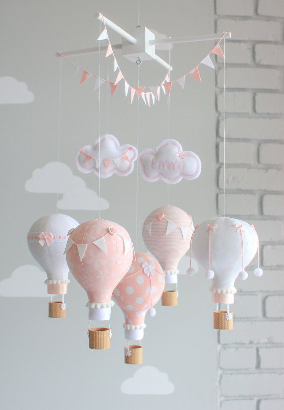 Pink and white baby mobile of little hot air balloons for a whimsical travel theme nursery decoration.  The photos show 5 hot air balloons floating under two puffy clouds. Each balloon is hand made from various coordinating fabrics and adorned with different bunting flags, bakers twine, buttons, pompoms and little baskets, printed using 3D technology, give it a real look of wicker. They all hang from a wooden mobile finished off with two strings of tiny bunting flags. You may personalize one…