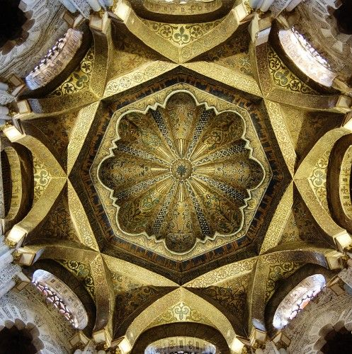 During the extension of the Mosque of Córdoba in 976 under the Spanish Umayyad Caliph al-Hakam II, this ribbed dome was erected over the mihrab, which indicates the direction of prayer. Entirely covered with glass and gold mosaics, its unique form was probably meant to recall a dome in the Umayyad mosque of Damascus, as were the mosaics, which were said to have been produced by a workman sent by the Byzantine emperor in Constantinople.