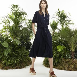 A fully buttoned mid-length polo dress with a drawstring waist inspired by tennis shoe laces. Sports fashion steps down off the catwalk and into the street.
