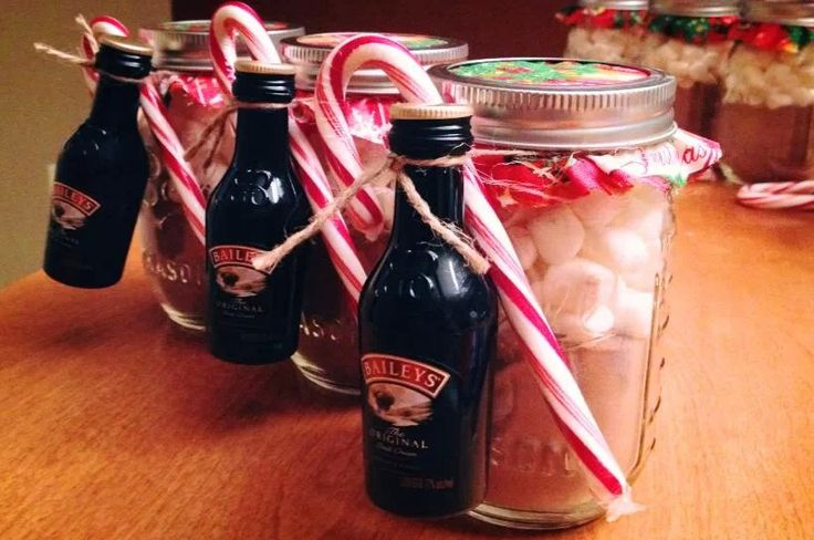 Hot coco with marshmallows in a mason jar. Candy cane and Bailey's on the side.