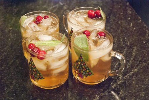 Yummy whiskey drinks made with ginger ale and sage simple syrup and garnished with cranberries and sage.