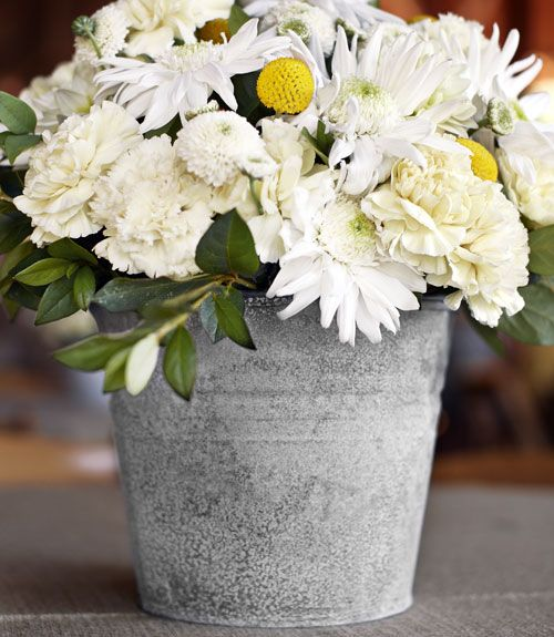 The designer struck a down-to-earth note by aging too-shiny galvanized buckets with a few spritzes of bleach. She suggests a similarly simple approach to arrangements: Unify flowers around a single hue, as in this grouping of white carnations and mums.