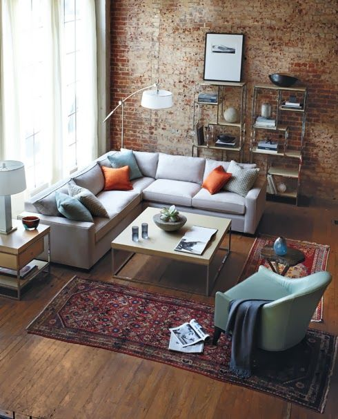 Exposed distressed brick, floor to ceiling windows, sectional grey couch and warm brown hard wood floors. The pefect place to curl up on a lazy day.