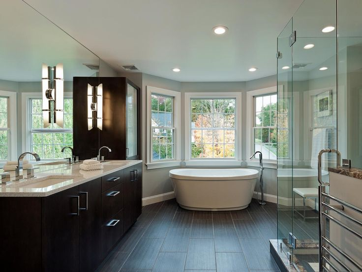 A mix of gleaming glass and warm natural materials give this enormous master bath a look that is at once airy and grounded. Designer Magued Barsoum created a focal point in the large space by nestling the freestanding tub in the semi-surround of the bay window; a large walk-in shower features Rainforest Green granite trim and a heated towel rack.