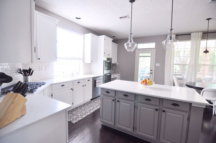 Finished kitchen renovation  Wall: Sherwin Williams Requisite Gray Cabinet paint: Behr Ultra Pure White Island paint: Benjamin Moore Winter Gates Pendant lights: Kichler (Amazon) Counter tops: Corian Rain Cloud
