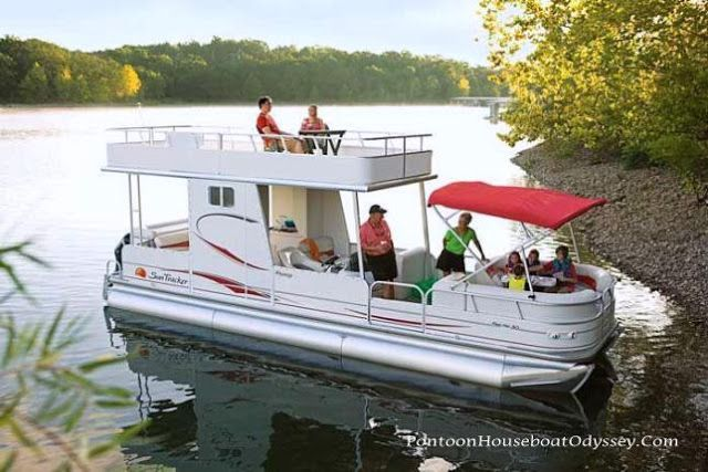 A pontoon boat with an upper deck with several family members enjoying quality outdoor time on their boat.