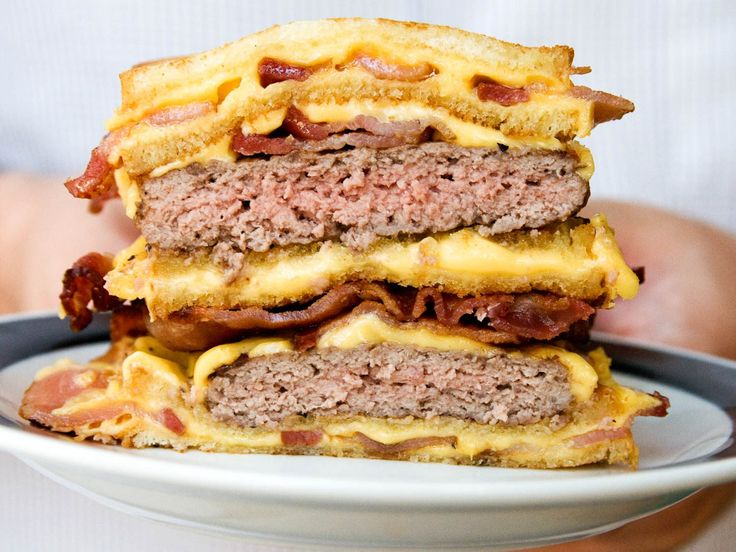 A double stacked burger with three mini bacon-filled grilled cheese sandwiches sandwiching it.
