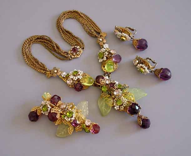"""HASKELL Hess parure composed of purple faceted crystal beads, chartreuse glass teardrops and glass leaves, it is enhanced by rhinestones, artificial pearls and filigree work. The necklace is 14 inches long with a 3 inch pendant, and the chains are darkened a bit with age but still lovely, circa 1950. The matching 2-1/2"""" wide brooch was created from vintage parts."""