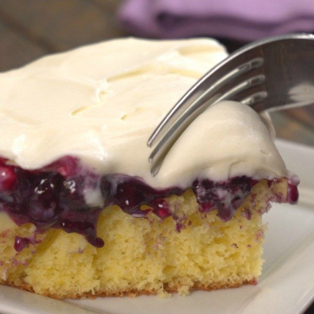 Fork going into piece of blueberry lemon pudding cake