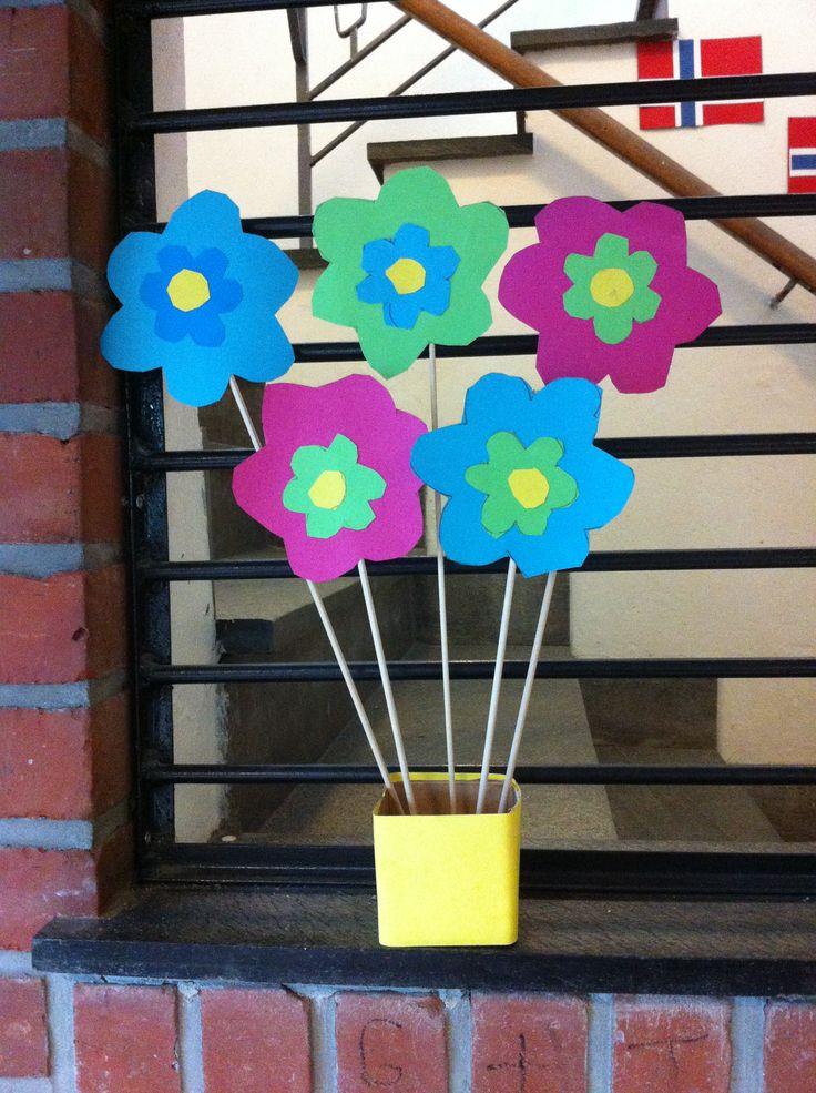 Vårblomster klippet ut av papp. De fikk velge mellom ulike farger. Lag maler til elevene for best resultat resultat. de limes til slutt på blomsterpinner.   Blomstervasen et laget av småmelkekartonger som er kledd i farget papir.