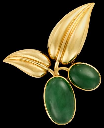 18 karat yellow gold jadeite brooch, Suzanne Belperron,  1940s.  Double 'berry' brooch, yellow gold leaves displaying two large jadeite cabochons, displaying hallmark for Societe Groene et Darde and French hallmark. #FreemansAuction