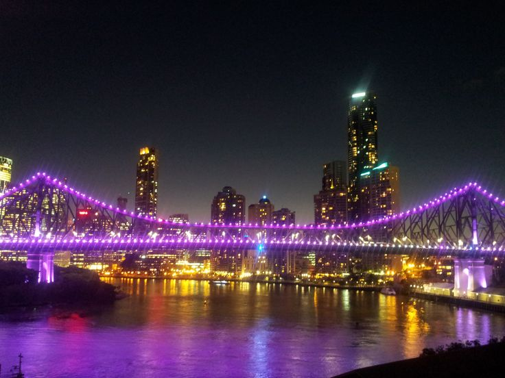Coloured lights on the Story Bridge from New Farm at night. Brisbane