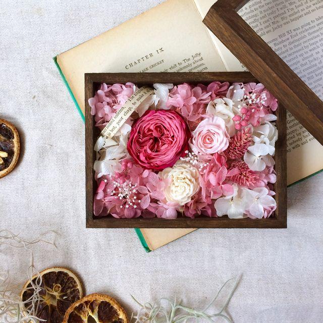 ダークブラウンに塗り込んだラスティック風の木箱。ピンクのアジサイ、小花、木の実などをたくさん詰め込んだ、可愛らしいフラワーボックスです。蓋を開けて楽しむもよし、閉じて楽しむもよし。。。小さな宝箱のようなお花を楽しんでいただけたらと思います。※木箱の蓋はア...