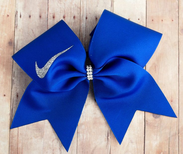 "This cheer bow is made with high quality US made 3"" grosgrain ribbon. The swoosh is made with silver glitter siser vinyl. This has 1 layer of ribbon and is sprayed with stiffener in order to keep it's"
