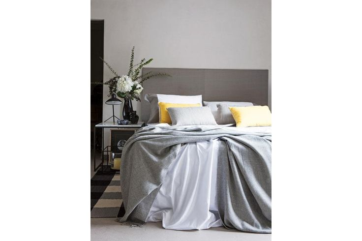 La ropa de cama en diferentes tonos de gris (Falabella) y alfombra rayada (Elementos Argentinos).  /Javier Picerno