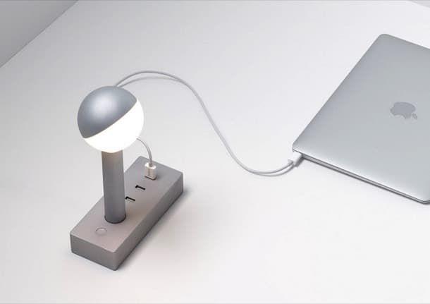 Busby W152: lámpara con conexiones USB. Sam Hecht y Kim Colin diseñaron Busby W152, una Lámpara LED con USB para recargar dispositivos. Puede funcionar como lámpara de mesa o lámpara de pared. Este diseño puede estar integrado en otros muebles. Se fabrica en dos versiones de pantalla, y dos colores: negro y aluminio. Los 3 puertos reconocen los requisitos de carga de los dispositivos conectados.  #Iluminación