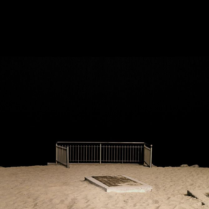 """Linus Lohoff's """"Sujets"""" is a series of photographs documenting the man-made structures that are frequently found at public beaches. Photographed in the dark, at night, under street lamps, these small buildings appear as isolated sculptures or art installations."""