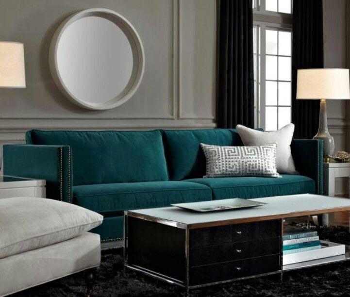 Deep teal sofa is a gem against grey walls, a dark rug ...