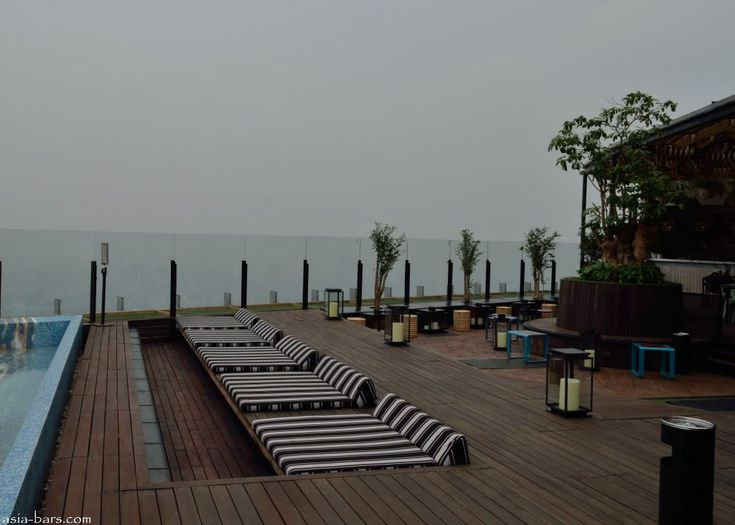 SKYE- Rooftop Restaurant & Lounge- spectacular new venue at the apex of Jakarta's tallest building.   Photo: Poolside daybeds set into the timber decking ( on an overcast & very hazy afternoon!)