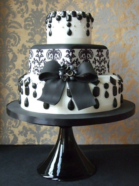 Very Classy Three Tier Gothic Black And White Wedding Cake Decorated With Black Hanging Gems And Hand Painted Scrolls Garnished With A Big Beautiful Black