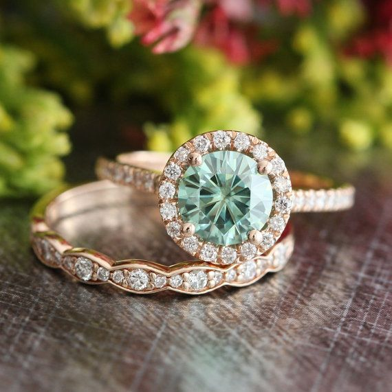 This unique bridal wedding ring set showcases a certified green moissanite engagement ring set in a solid 14k rose gold halo diamond ring setting.