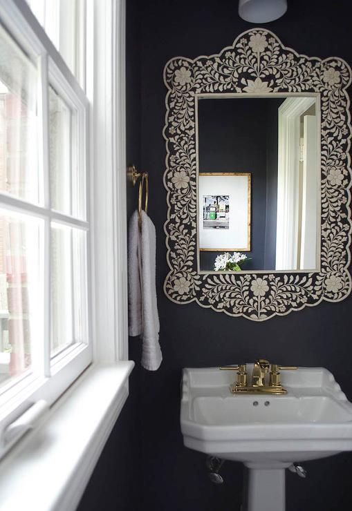 Black and white powder room boasts walls painted black lined with a Wisteria Embossed Bone Flower Mirror over a pedestal sink fitted with a gold faucet kit alongside a gold towel ring.