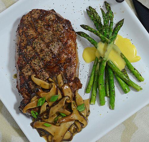 Prime ribeye steak with shiitake mushrooms and asparagus with Hollandaise sauce.