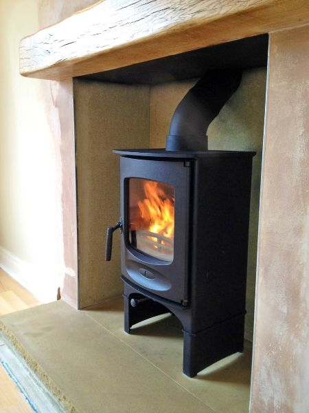 Charnwood C-FOUR on log store with oak fireplace beam and Yorkshire stone hearth connected to twin wall insulated flue.