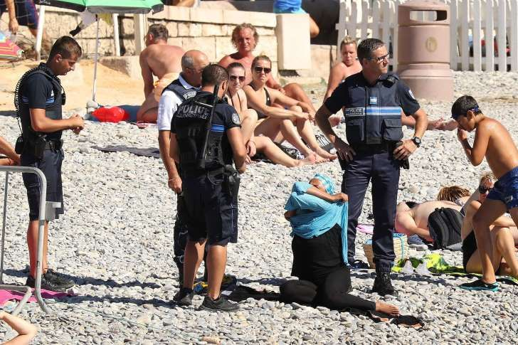 Police fine a woman for wearing a burkini on the Promenade des Anglais beach in…