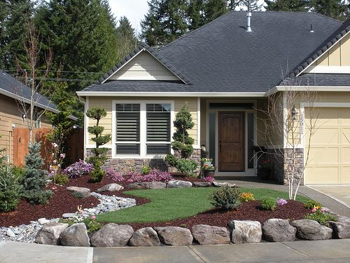 front yard. Low maintenance landscaping. Like the contrast of lawn, beauty bark, and rock river.