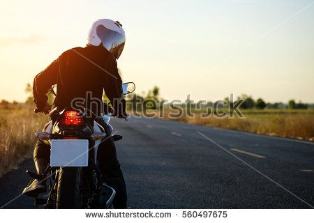 a man on the motorcycle parking on the road left side and sunset, to looking behind.