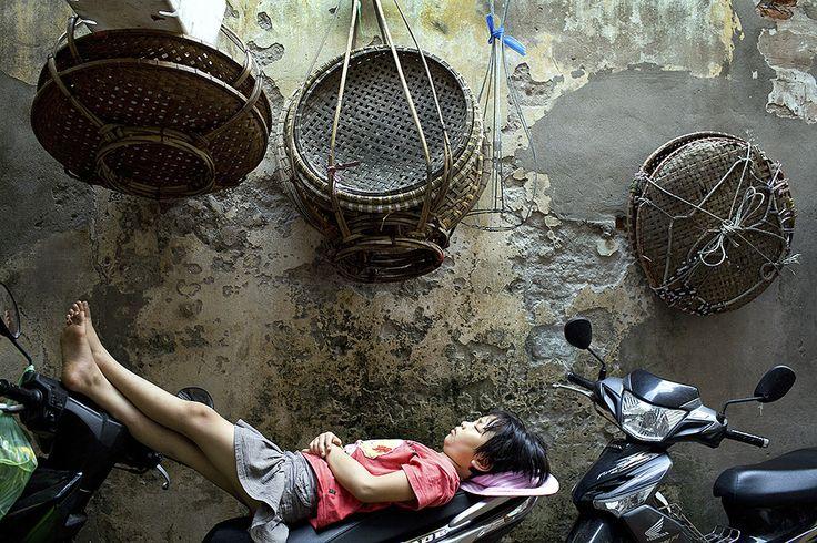 Young girl catches a nap in a Hanoi lane, Vietnam - Ein Mädchen schäft kurz auf einer Straße in Hanoi, Vietnam.