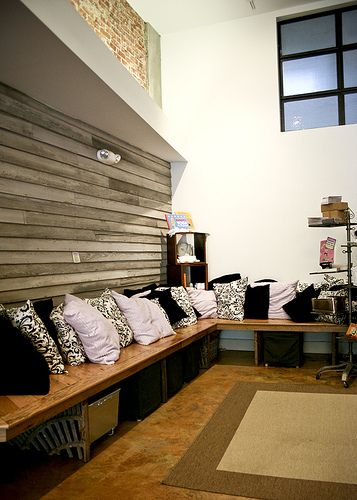 Tranquil Space Yoga Studio. stained concrete floor. custom bench made of repurposed materials. sitting area.