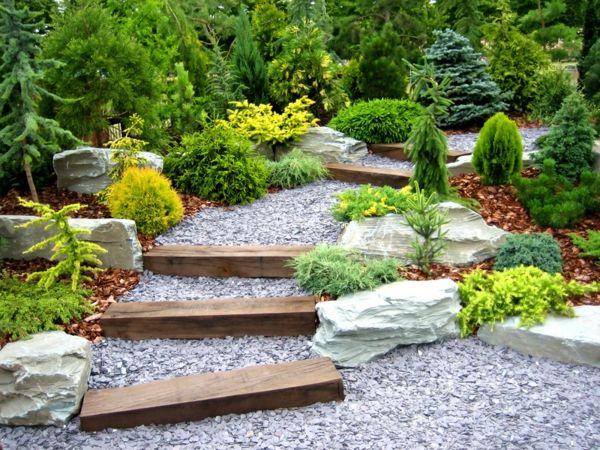 diy treppen in einem garten mit kies und vielen grünen pflanzen - gartengestaltung mit rollkies
