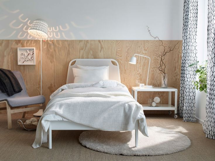 A white bed with fabric headboard and bed textiles in white (love that lamp)- IKEA
