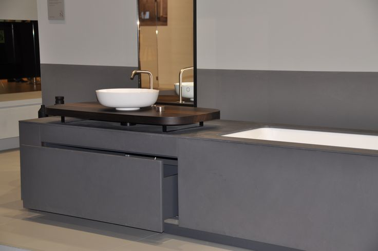 MANHATTAN is an integrated Bathtub Washbasin system for the bathroom in grey eco-cement, characterized by an innovative console in smoked oak, a vertical mirror, OX taps in stainless steel 316L and a push to open drawer.