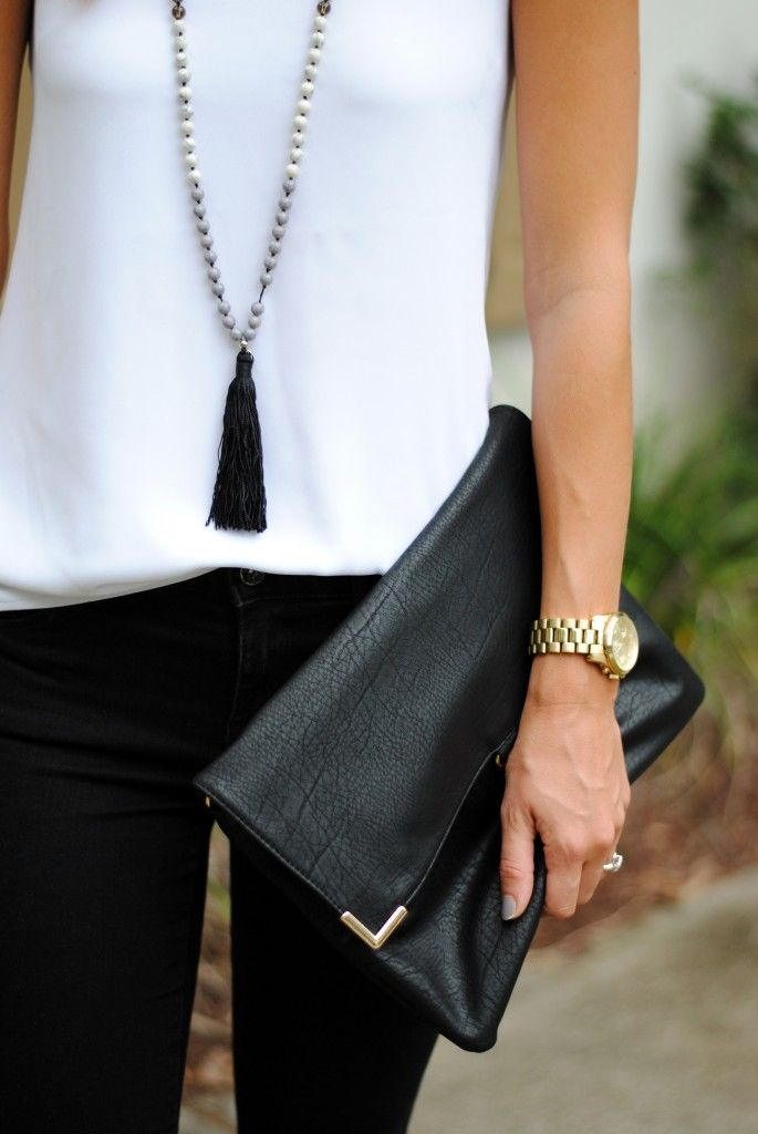 Long black tassel necklace and black envelope clutch with small metal detail.